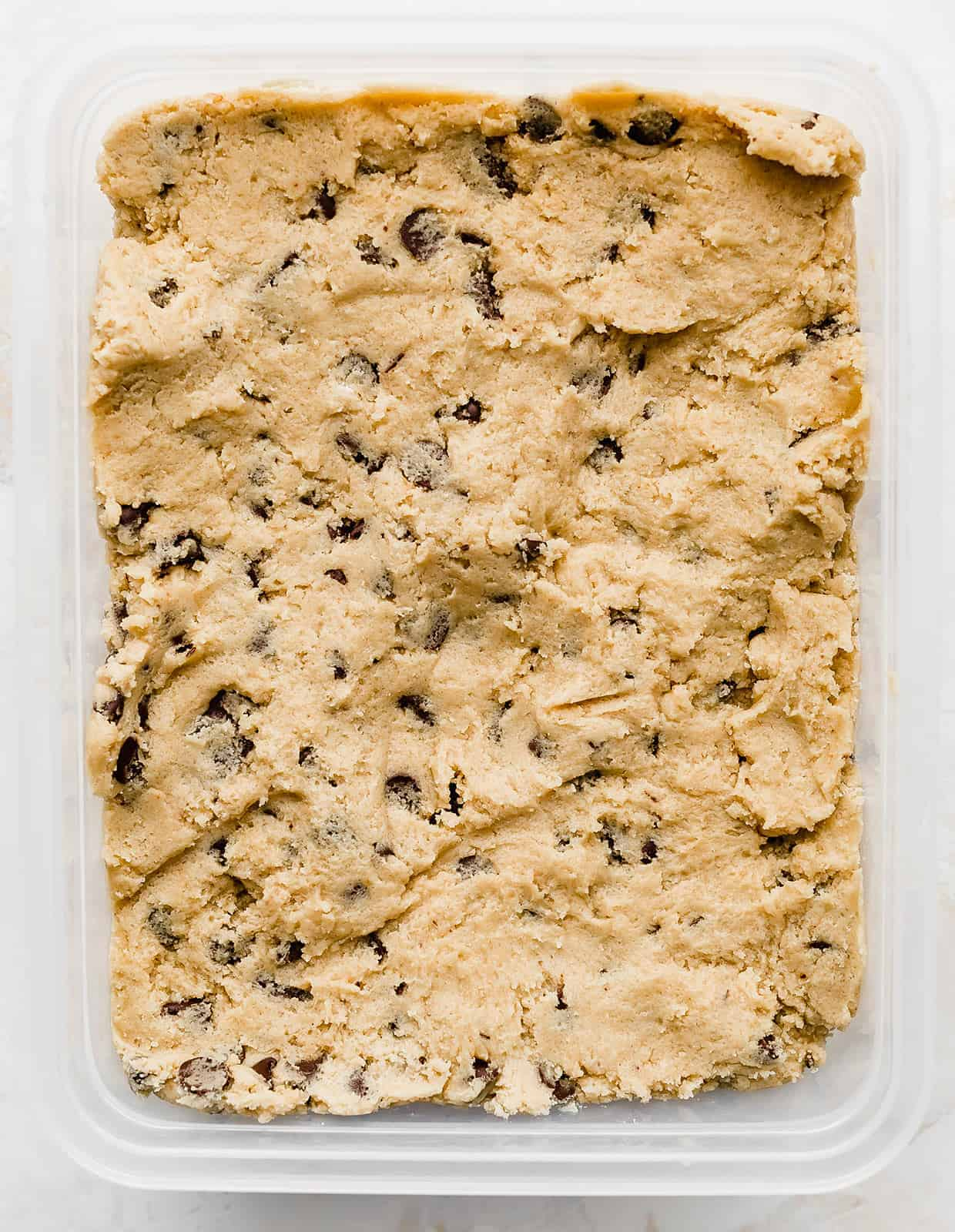 Chocolate Chip Cookie dough batter in a rectangular Tupperware.