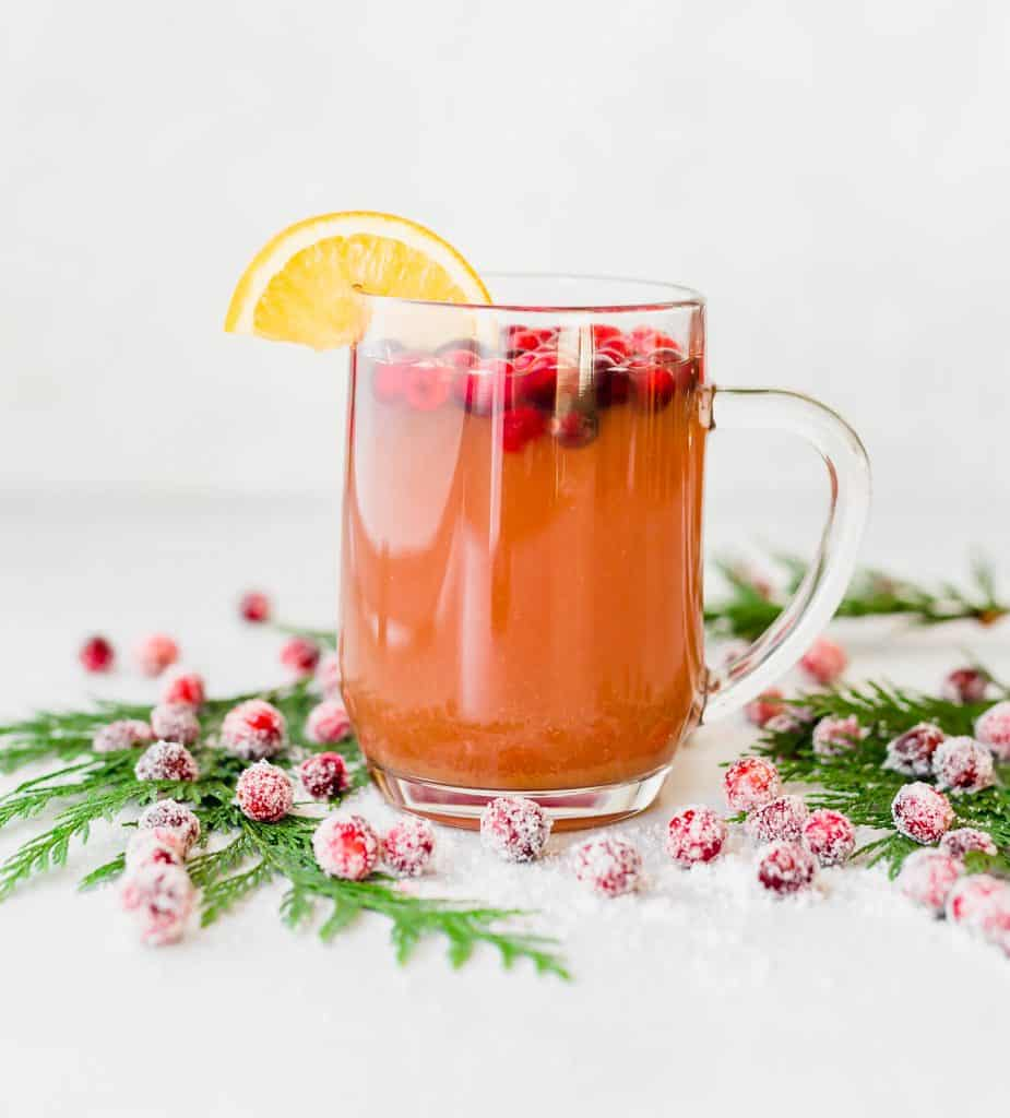 Cranberry Apple Cider with sugared cranberries at the base of the mug.