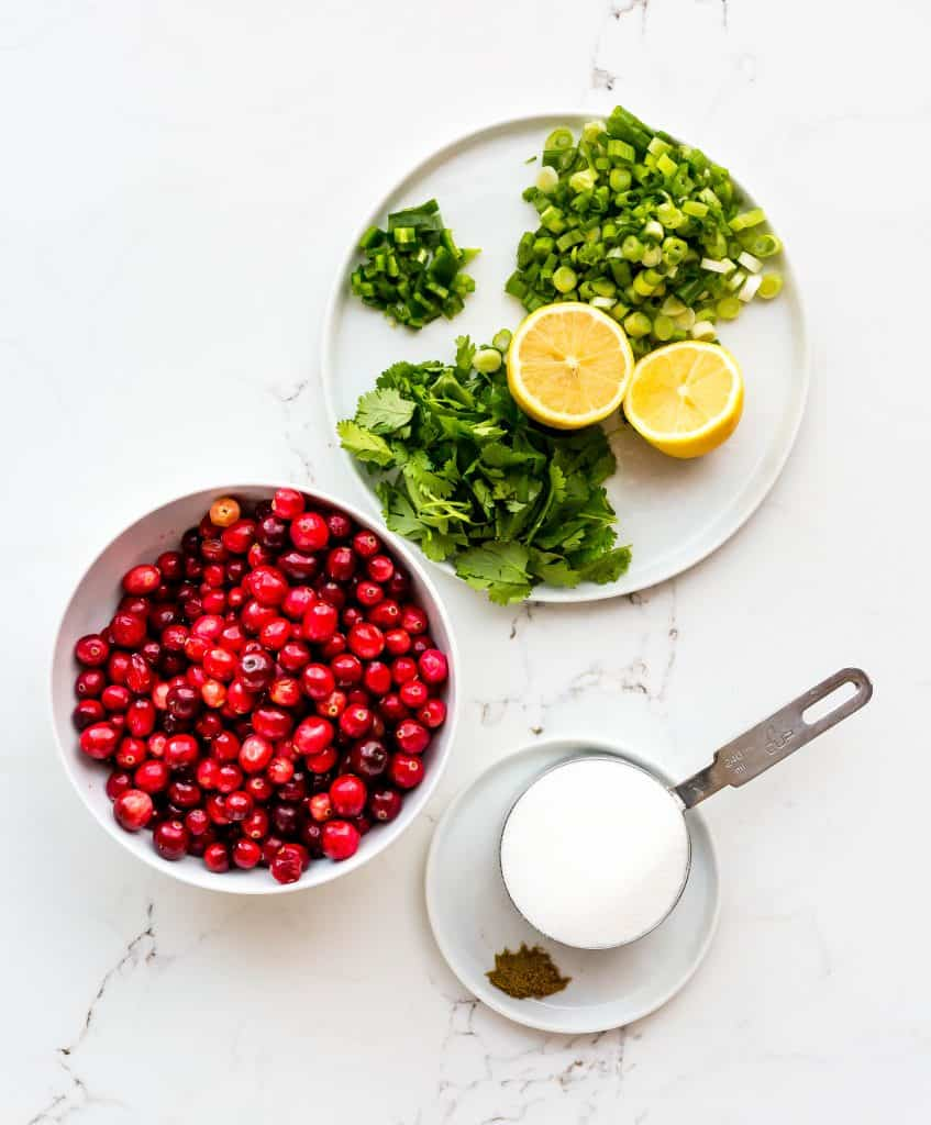 Spread of cranberries, cilantro, green onions, lemons, and sugar for Cranberry Cilantro Dip.