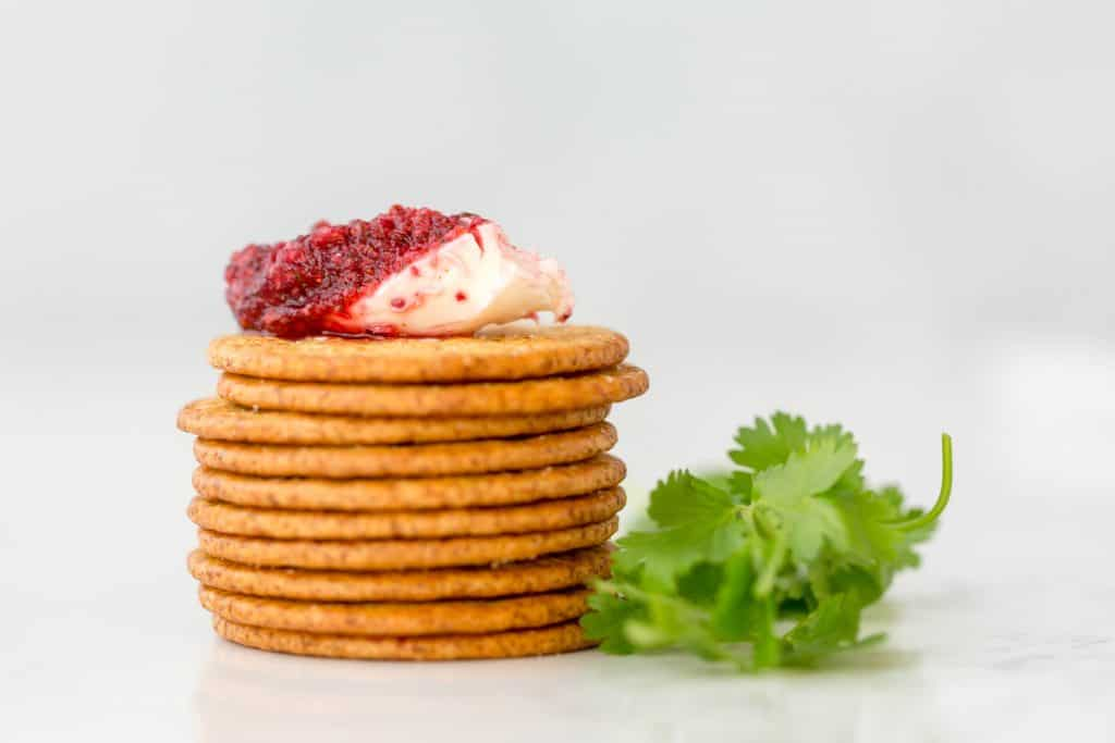 A generous spread of cranberry cilantro dip on a cracker.