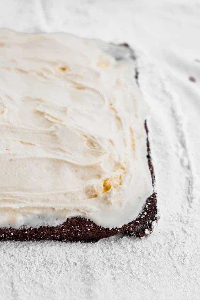 Chocolate sheet cake with vanilla ice cream spread on top.