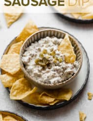 A bowl of cream cheese sausage dip with a tortilla chip in the dip.