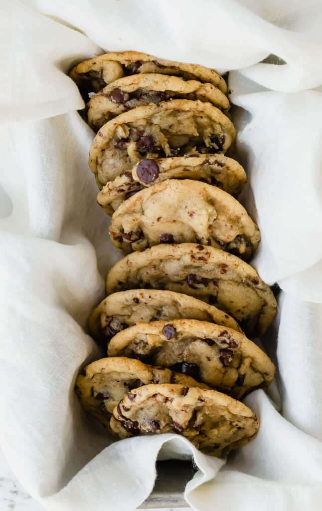 Chocolate chip cookies resting on a napkin in a bread pan.