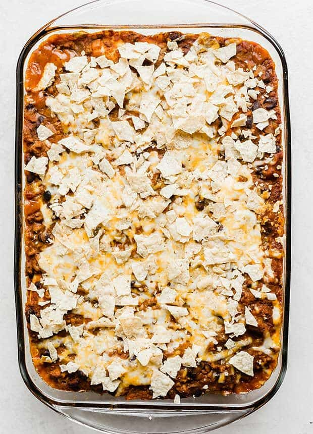 Mexican lasagna topped with crushed tortilla tips and shredded cheese.