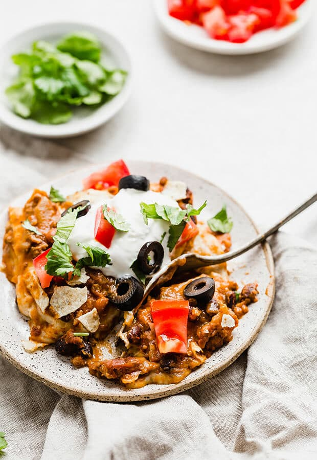 Mexican Lasagna topped with sour cream, cilantro, tomatoes, and olives.