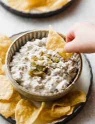 A hand dipping a chip into sausage dip.