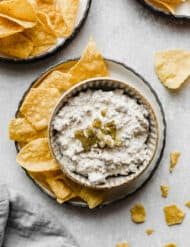 Sausage dip in a bowl with tortilla chips surrounding it.