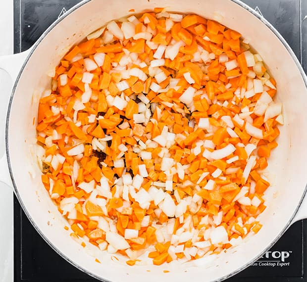 A pot with diced onions and carrots for making sausage and tortellini soup.