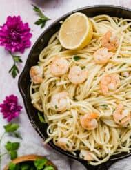 A skillet full of shrimp scampi with linguini.