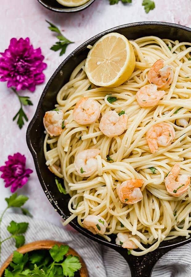 A skillet full of shrimp scampi with linguini.