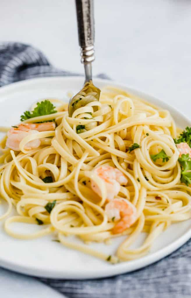 Shrimp Scampi with Linguini and a fork twisting noodles.
