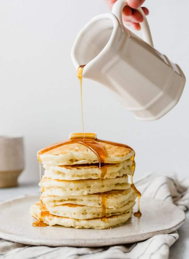 A stack of fluffy buttermilk pancakes with maple syrup being drizzled over top.