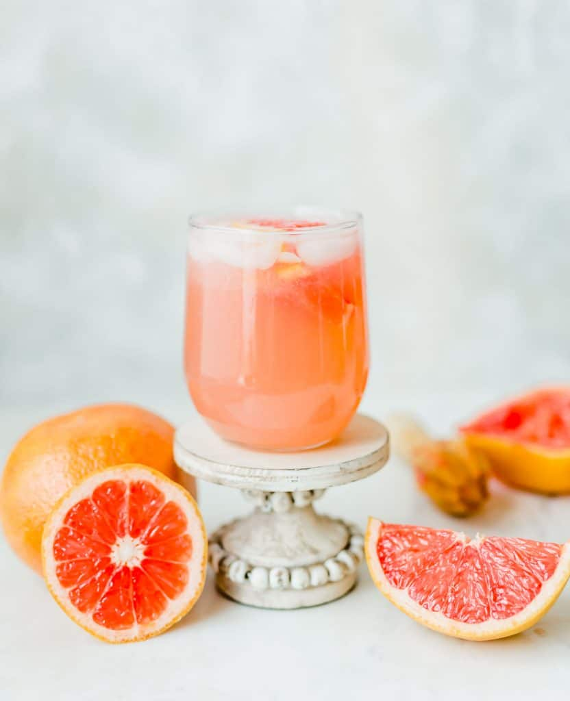 Grapefruit Italian Soda in a clear glass, with grapefruit surrounding the drink.