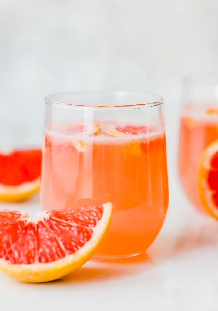 Grapefruit Italian Soda with a grapefruit wedge sitting in front of the glass.