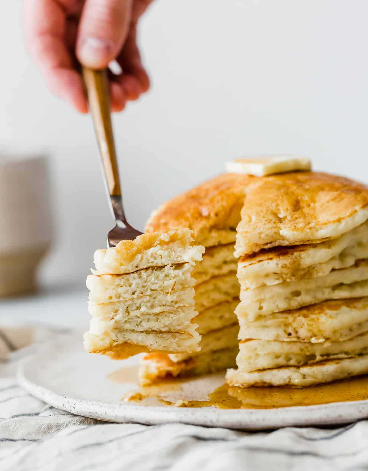 A fork holding a bite of pancake, with a stack of pancakes in the background.