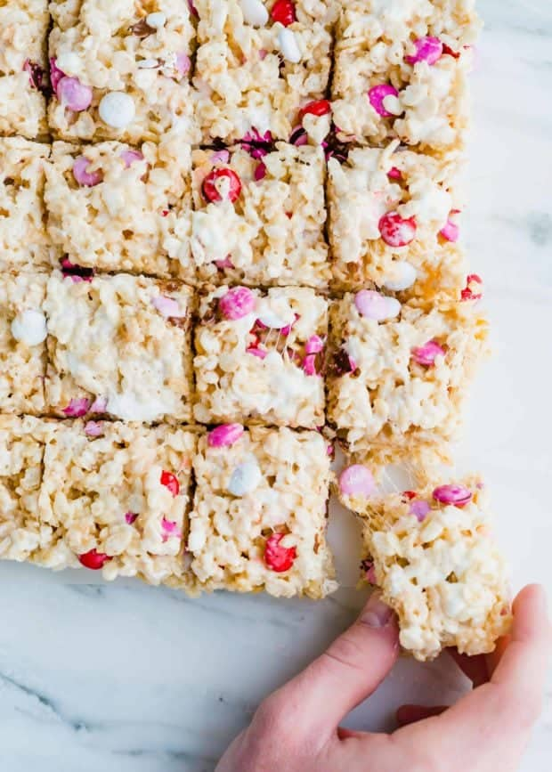 Hand grabbing a Rice Krispie treat with red, pink, and white M&M's.