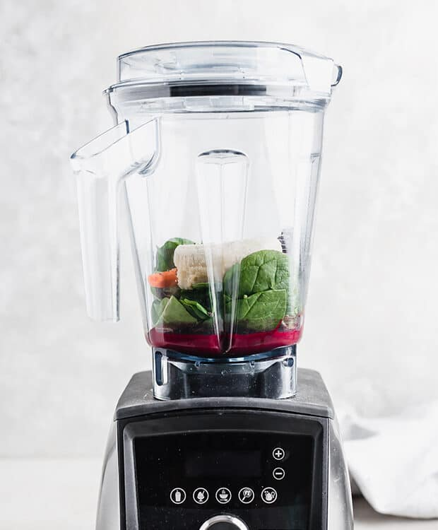 A blender cup sitting on the blender attachment with spinach, carrot, açaí juice, banana, and blueberries in it.