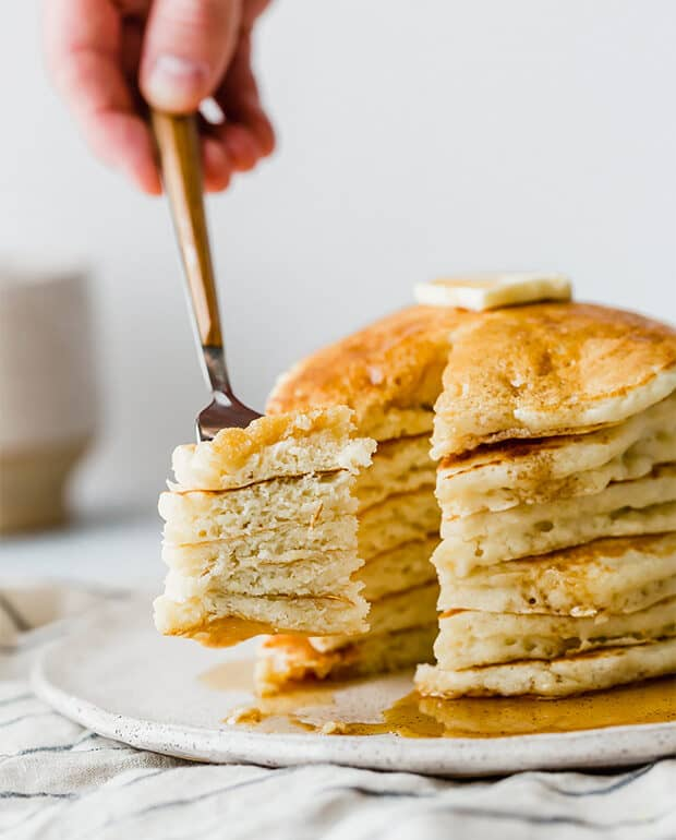 A fork carrying a bite of homemade buttermilk pancakes.