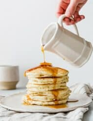 Maple syrup being drizzled over a stack of pancakes.