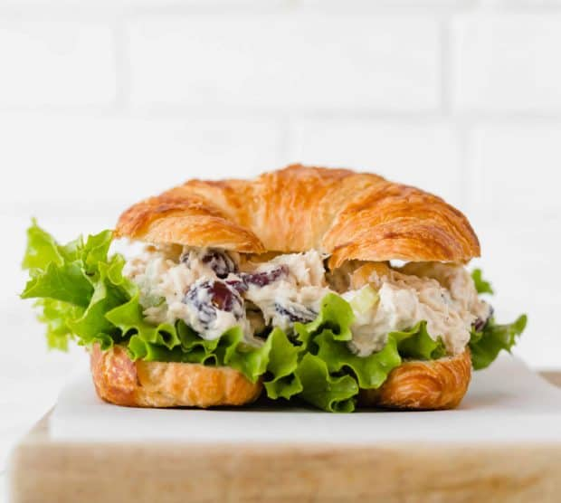 Chicken Salad Sandwich with leafy green lettuce on a croissant.