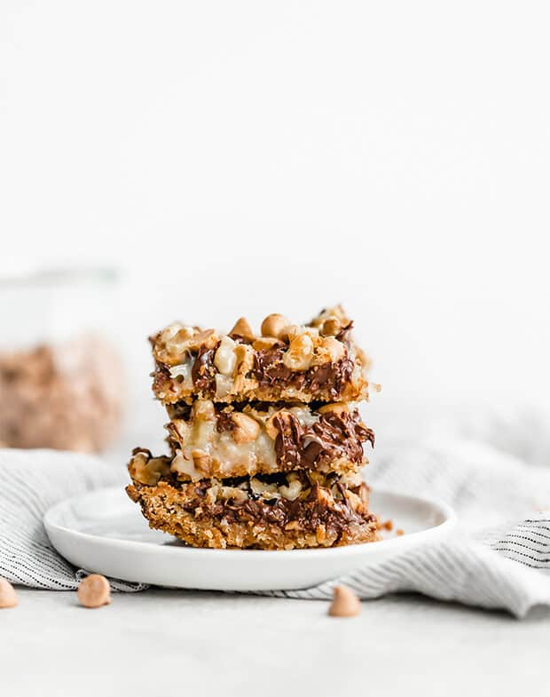 A stack of 7 layer bars on a small white plate.