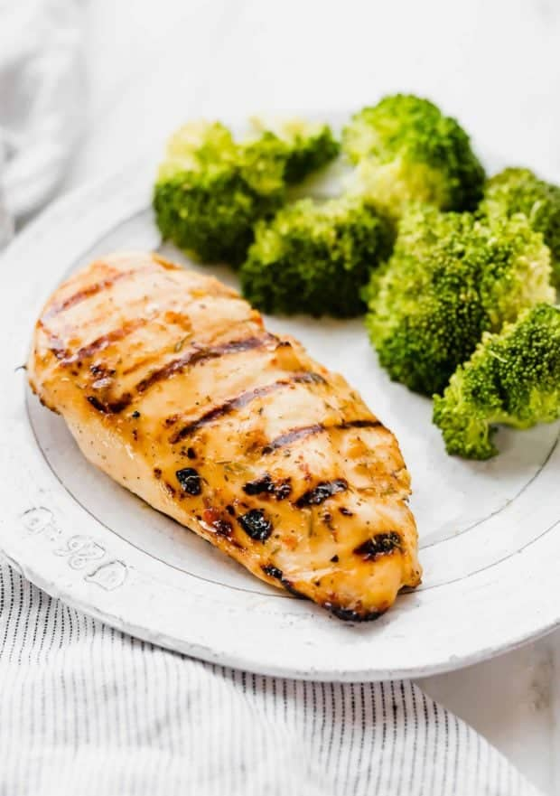 A grilled Italian chicken breast on a white plate.