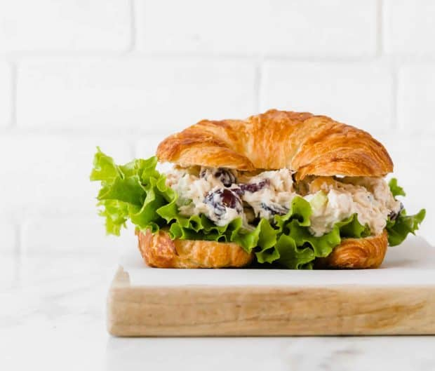 A croissant stuffed with chicken salad recipe and leafy green lettuce, sitting on a wooden cutting board.