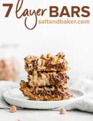A stack of three 7 layer bars on a white plate.