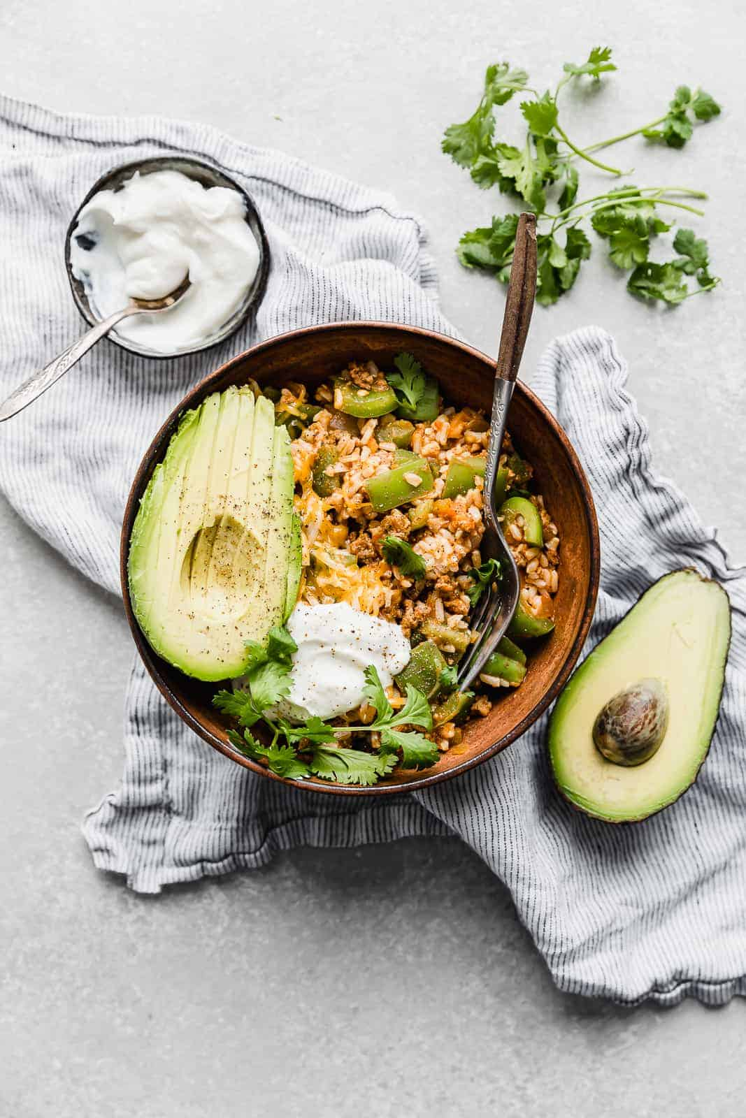 Deconstructed Stuffed Peppers in a brown bowl with a sliced avocado and cilantro for garnish.