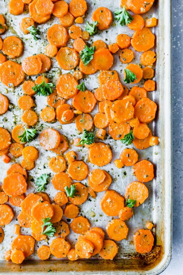 Sliced carrots scattered on a sheet pan, garnished with fresh parsley.