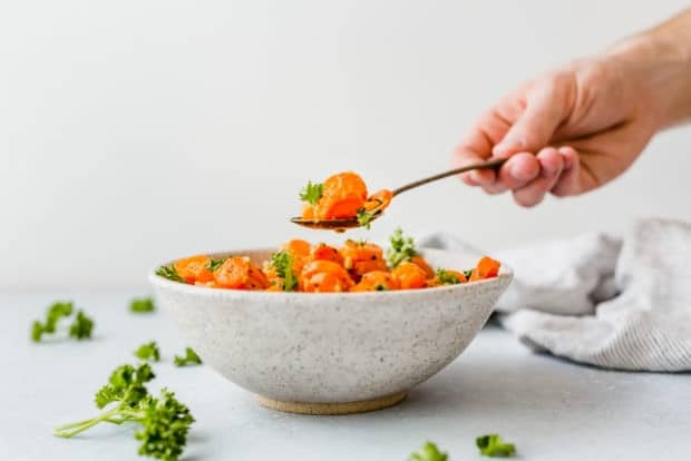 Bowl of roasted carrots garnished with fresh parsley, with a hand holding a spoon mid air cradling some carrots.
