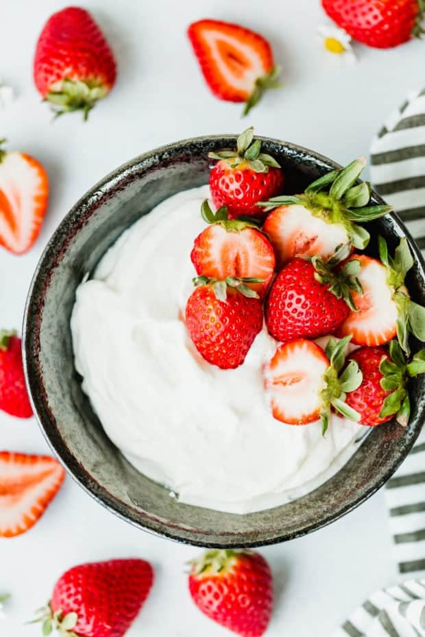 This Greek Yogurt Whipped Cream is beyond refreshing! Add strawberries, peaches, or the fruit of your choice and you have an easy and delicious dessert!