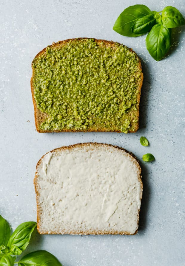 Two slices of whole wheat bread, one slice with basil pesto spread along the surface and the other with mayo.