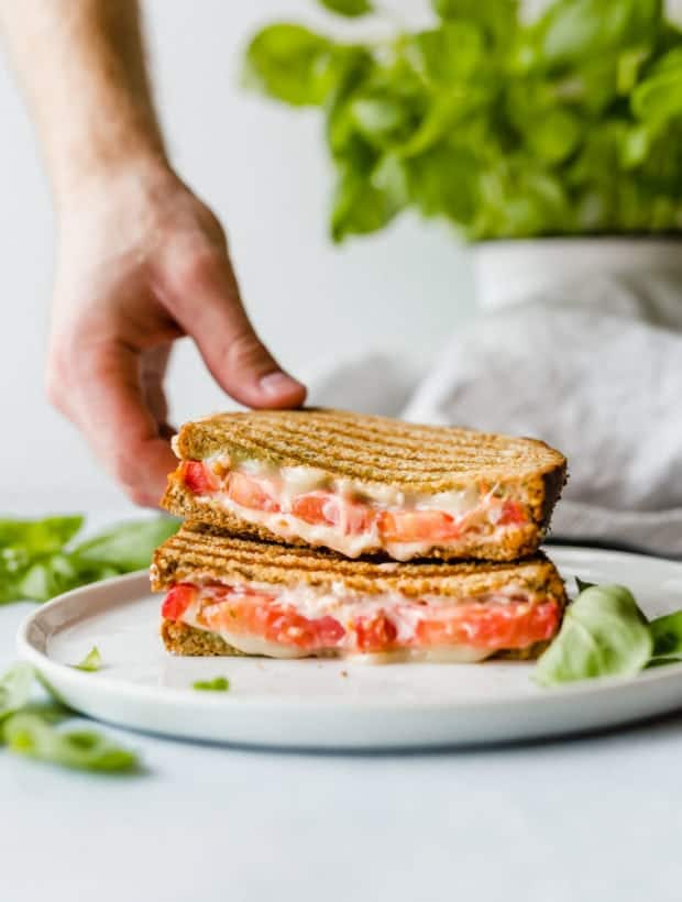 A grilled tomato sandwich halved, with a hand reaching to grab one half of the sandwich.
