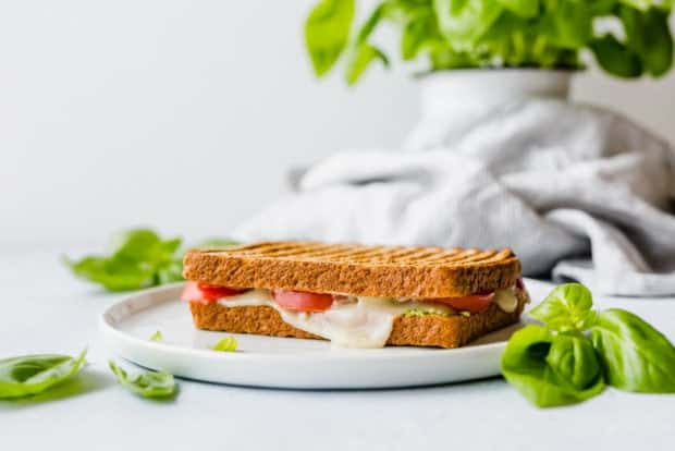 A grilled sandwich with melted mozzarella and fresh tomatoes visible between the slices of bread.