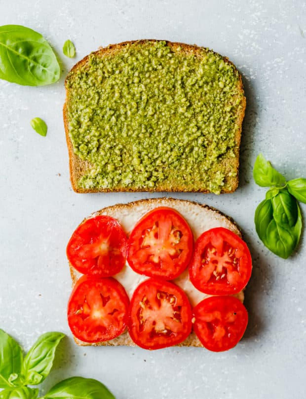 Two slices of bread, one covered in basil pesto and the other has 6 slices of fresh Roma tomatoes on top.