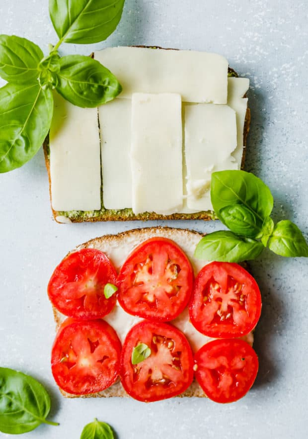 Two slices of bread, one slice covered in sliced mozzarella and the other with 6 slices of fresh tomatoes.