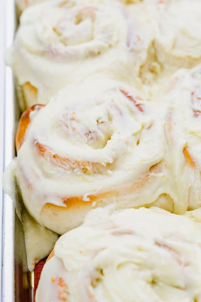 Freshly frosted orange sweet rolls.