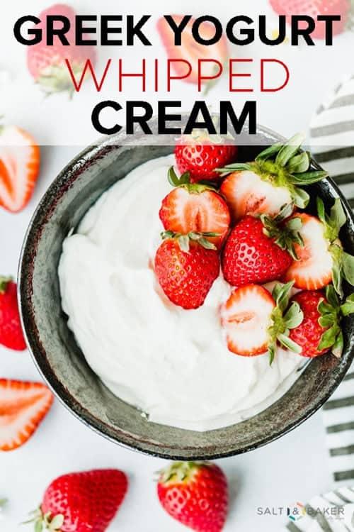 Black bowl with greek yogurt whipped cream and fresh strawberries as garnish.