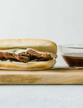 Slow Cooker French Dip Sandwiches with a cup of au juice next to the sandwich.