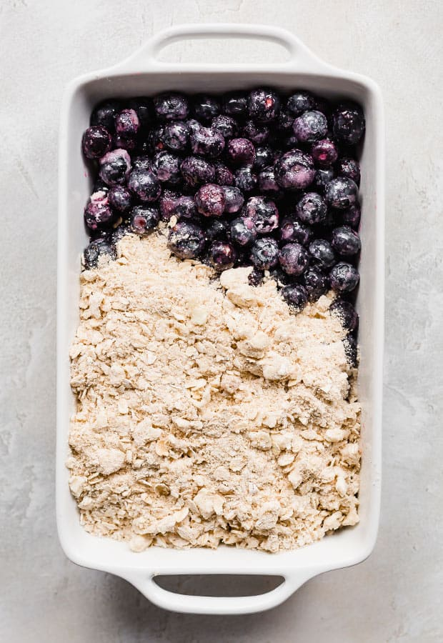 A white baking dish full of blueberries topped with an oat crumble.