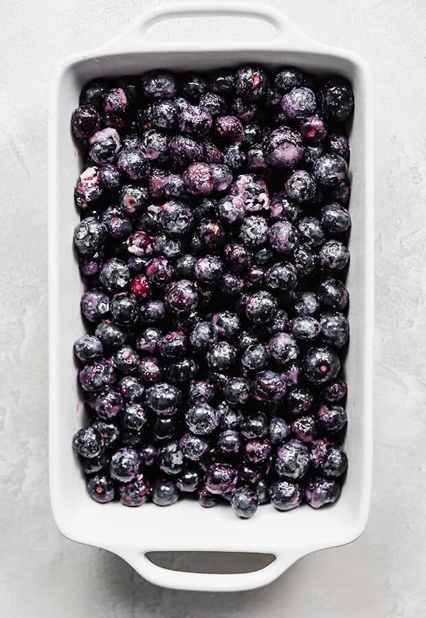 A rectangular baking dish full of blueberries.