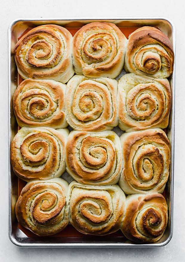A baking sheet full of freshly baked orange rolls.