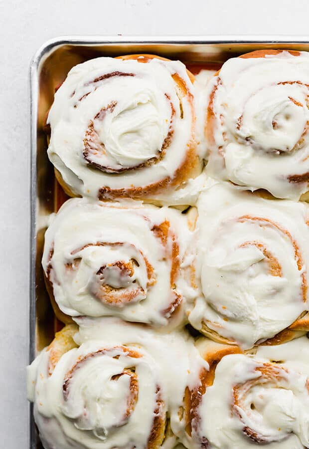 A close up photo of homemade orange rolls covered in frosting.
