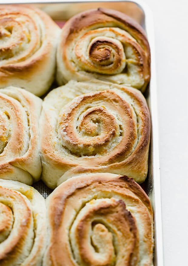 A close up photo of a freshly baked orange roll.