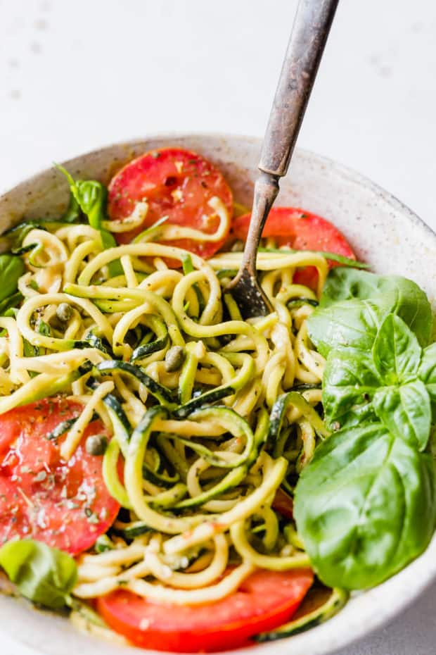 Delicious zucchini noodles are used to make this 5-Minute Cheesy Zucchetti Bowl from Cotter Crunch's new cookbook! This dish takes 5 minutes to make, is gluten-free, and low carb!