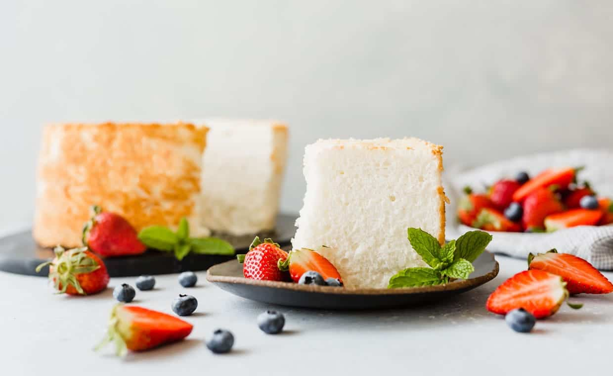A slice of angel food cake on a plate, with strawberries and blueberries throughout the scene.