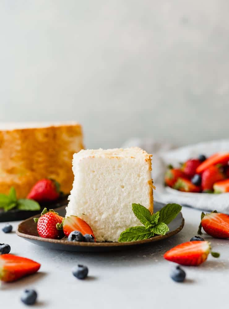 A slice of angel food cake on a black plate, with strawberries and blueberries scattered throughout the scene.