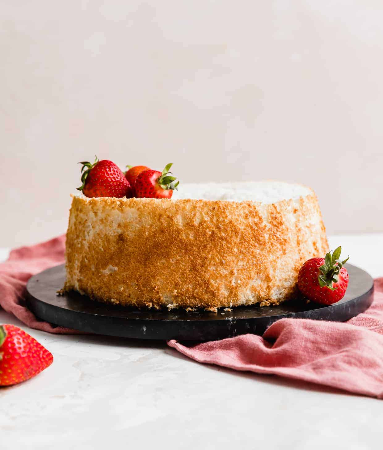 An angel food cake on a black round platter.