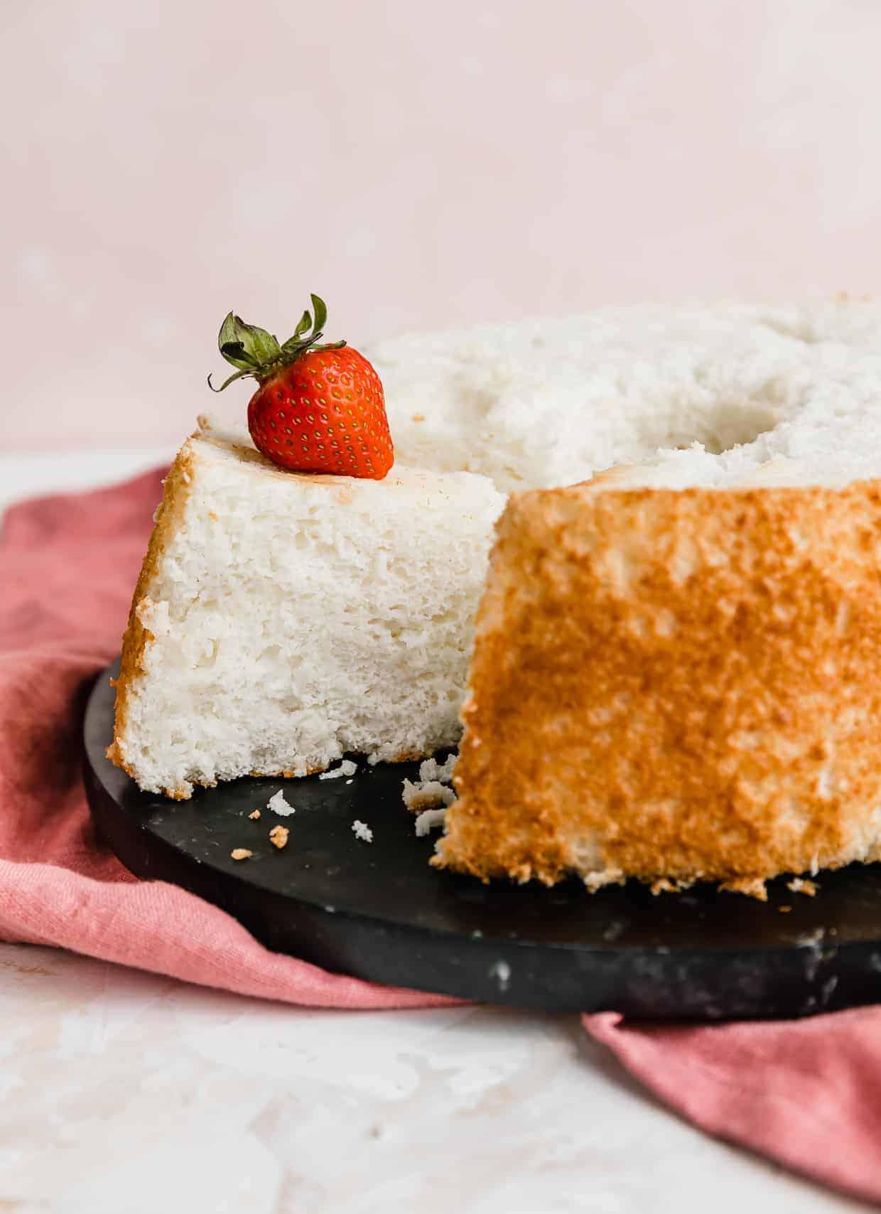 A homemade angel food cake on a black plate.